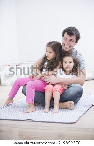 Smiling young man with daughters sitting in his lap at home - stock photo