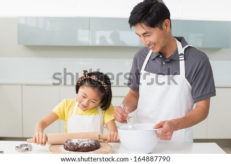Smiling young man with his daughter preparing cookies in the kitchen at home - stock photo