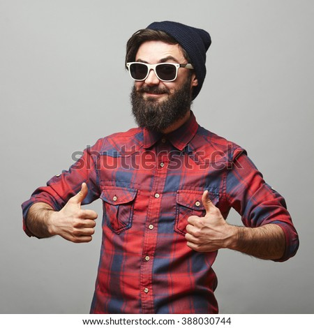 Smiling young man with long facial hair giving thumbs up sign. Happy hipster man with beard and sunglasses showing ok gesture. - stock photo