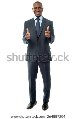 Smiling young man with showing thumbs up - stock photo