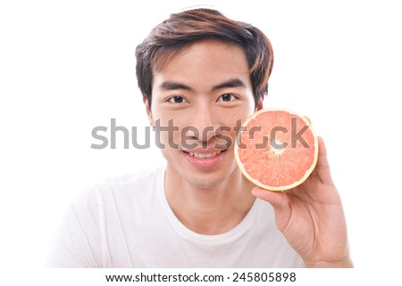 Smiling young man with sliced grapefruit in her hands