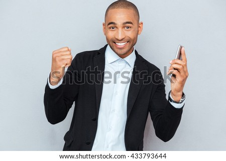 Smiling young man with smart phone isolated on grey background - stock photo