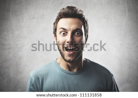 Smiling young man with surprised expression - stock photo