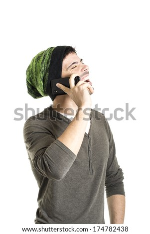 Smiling young man with wool cap talking on the cell phone isolated on a white background - stock photo