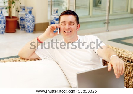 Smiling young man working on laptop computer and call by phone at home - stock photo