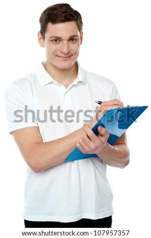 Smiling young man writing on notepad and looking at camera