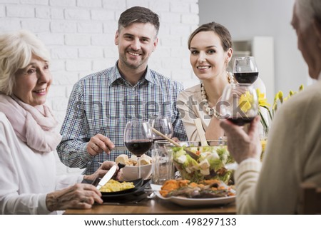 Smiling young marriage sitting at a dinner table with their parents, drinking wine and enjoying themselves