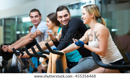 Smiling young men and women riding stationary bicycles in fitness club