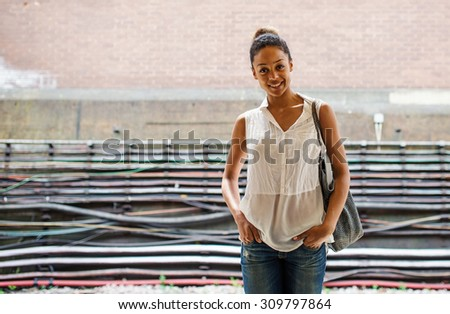 Smiling young mixed race woman portrait inside underground in London. - stock photo