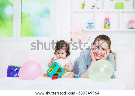 Smiling young mom lying on front in the bed, looking at camera while her baby little girl playing with a baby toys.Shallow doff, focus at mother. - stock photo