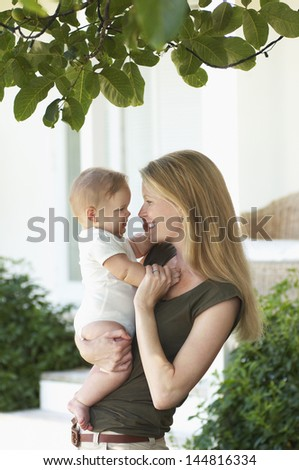 Smiling young mother and baby standing under tree - stock photo