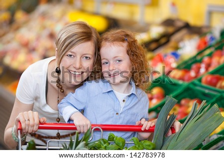 Smiling young mother and daughter shopping for fresh fruit and vegetables in a supermarket - stock photo