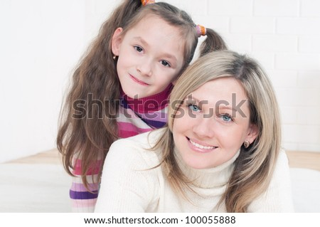 Smiling young mother and her daughter having fun at home