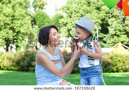 Smiling young mother and little son eating ice-creams together in a summer park