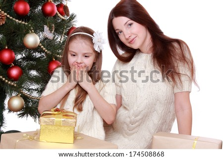 Smiling young mother and lovely little girl having fun time on Christmas time/Happy mother and daughter on Holiday theme - stock photo