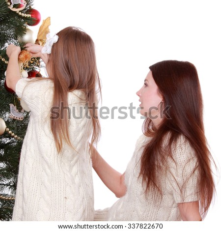 Smiling young mother and lovely little girl having fun time on Christmas time/Happy mother and daughter on Holiday theme
