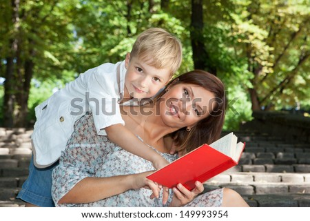 Smiling young mother and son reading book together in a summer park - stock photo