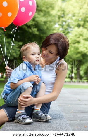 Smiling young mother and son spend time together in a summer park - stock photo