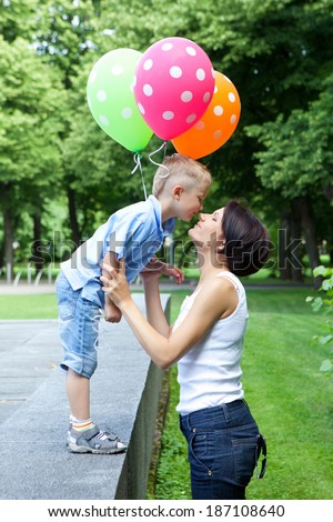 Smiling young mother and son spending time together in the park - stock photo