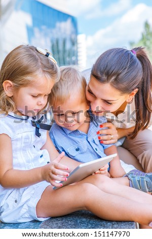 Smiling young mother and two little siblings watching tablet - stock photo