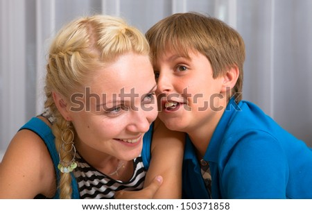 Smiling young mother has a good time in conversations with the son