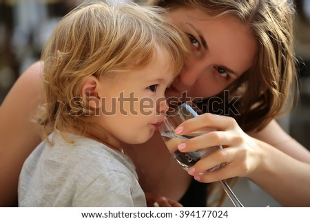 Smiling young mother holding glass and child boy with blonde hair drinking water from paret hands sunny day outdoor, horizontal picture - stock photo