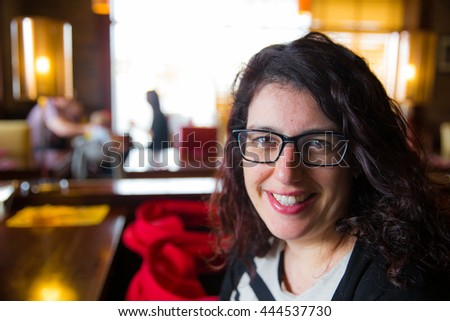 Smiling young mother sitting in a restaurant with her pushchair next to her - stock photo