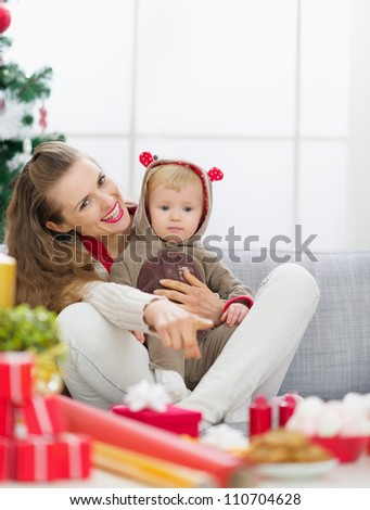 Smiling young mother spending Christmas with baby and pointing on copy space - stock photo