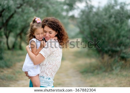 Smiling young mother with a baby in nature - stock photo