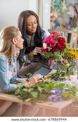 smiling young multiethnic florists working with digital tablet and flowers in flower shop