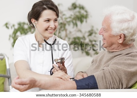 Smiling young nurse taking old man's blood pressure - stock photo