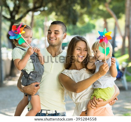 Smiling young parents holding kids with toy windmills at summer day - stock photo