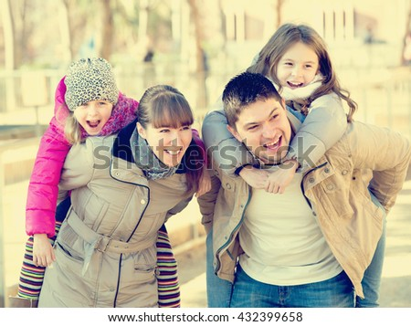 Smiling young parents playing with little daughters at slide of playground. Focus on parents - stock photo