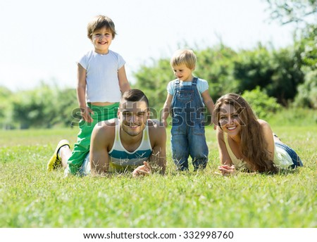 Smiling young parents with children laying in summer grass