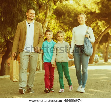 Smiling young parents with two children walking in the european city