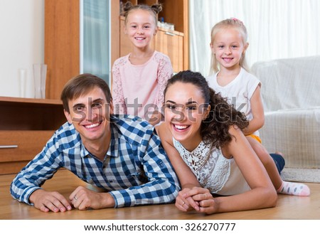 Smiling young parents with two little daughters laying on the floor at home