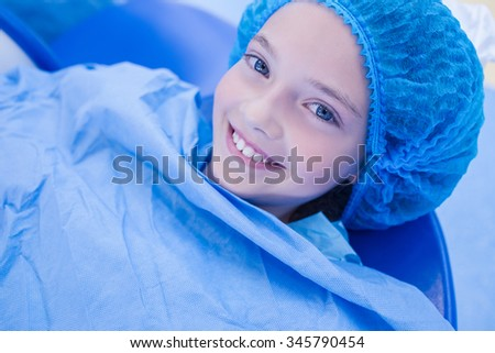 Smiling young patient lying on the dentists chair at the dental clinic - stock photo