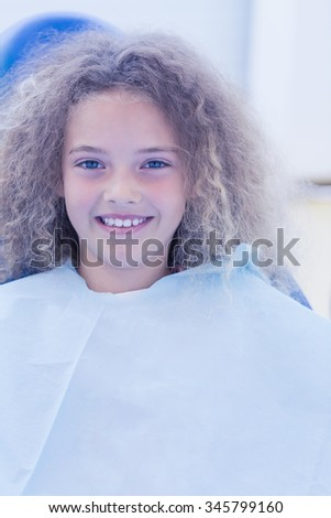 Smiling young patient sitting in dentists chair at the dental clinic