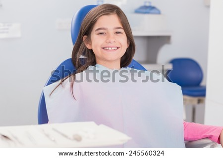 Smiling young patient sitting in dentists chair in dental clinic - stock photo