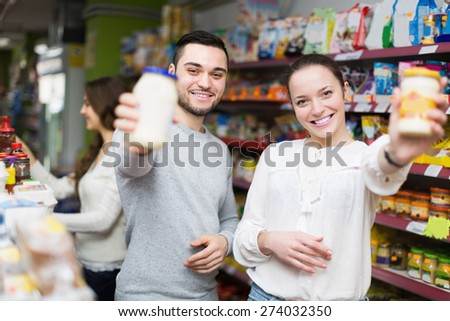 Smiling young people choosing tinned food at supermarket - stock photo