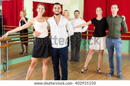 Smiling young people dancing waltz in the hall - stock photo