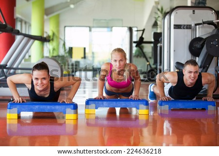 smiling young people doing exercises at gym on steeper - stock photo