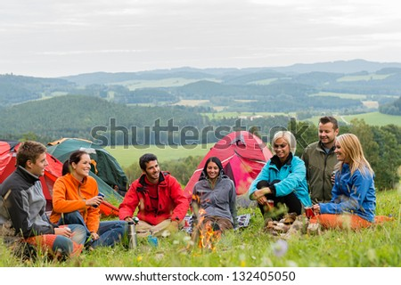 Smiling young people enjoying nature beside tents and scenic view - stock photo