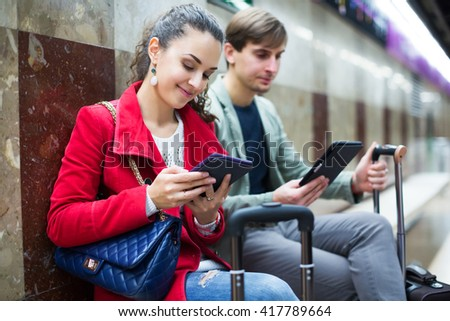 Smiling young people with tablet and smarthphone at metro station - stock photo