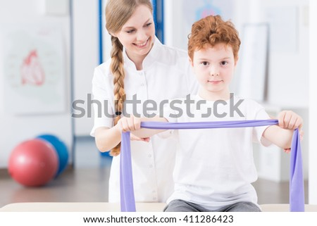 Smiling young physiotherapist and her little patient exercising arms with elastic band