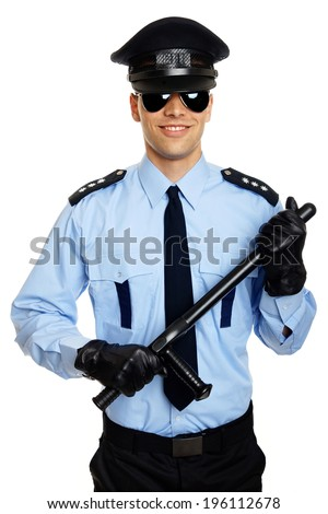 Smiling young policemen in uniform holds nightstick at hands - stock photo