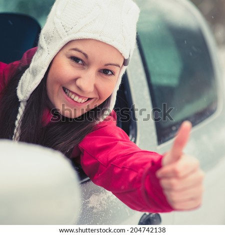Smiling young pretty woman in the car - safe winter driving concept - stock photo