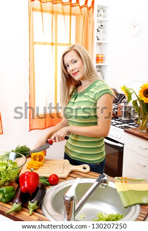 Smiling young pretty woman preparing salad in the kitchen - stock photo