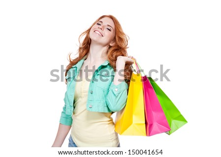 smiling young redhead girl with colorful shoppingbags  isolated on white background