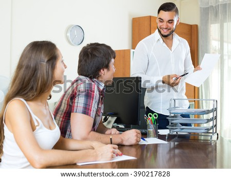 Smiling young salesman telling to colleagues about the project in the office